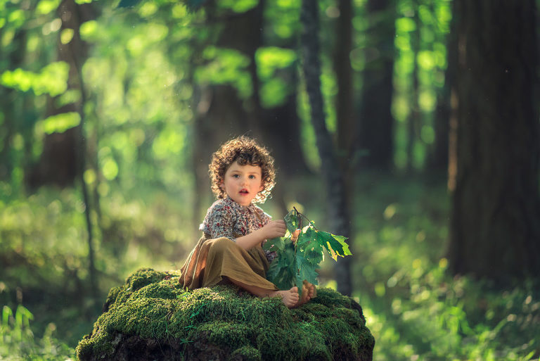 Little girl on mossy stump