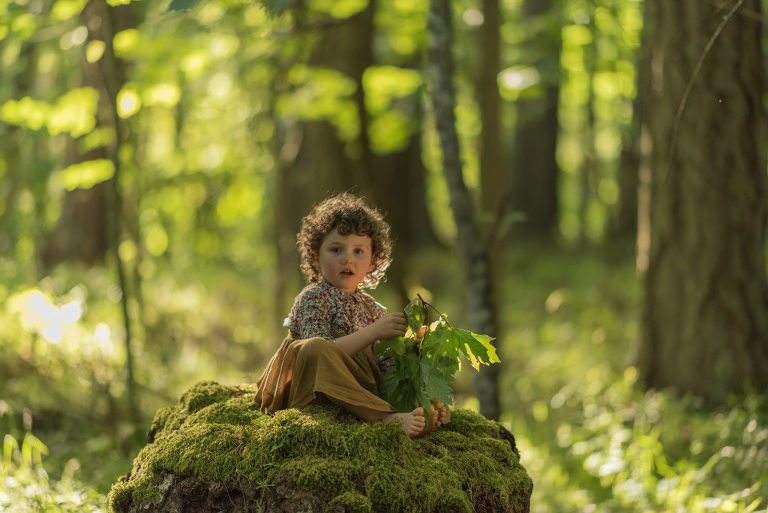 Girl on mossy tree stump
