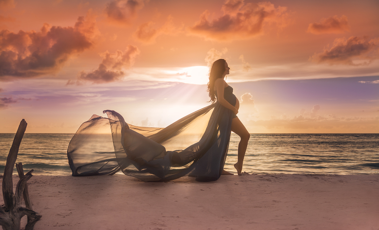 Pregnant woman on beach in flowing gown